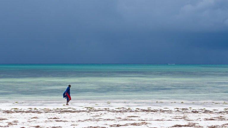 Een masai loopt op het strand van Zanzibar