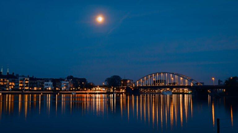 De brug van Deventer in de schemering met maan.