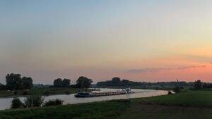 Een boot op de IJssel in avondlicht bij Cortenoever