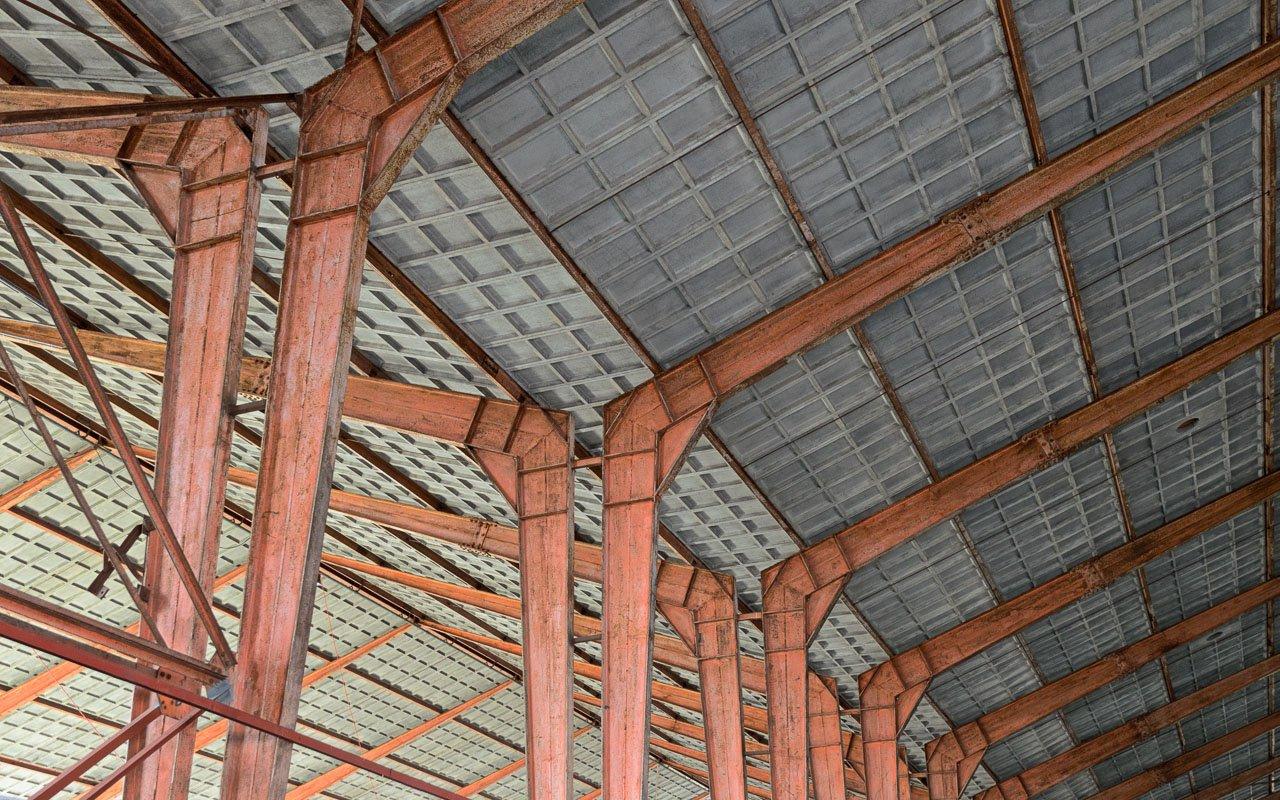 De spanten en het grijze plafond van een loods in de voormalige zwitsal fabrieken aan de Vlijtseweg in Apeldoorn