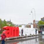 Toeristen poseren in de regen voor I am Amsterdam