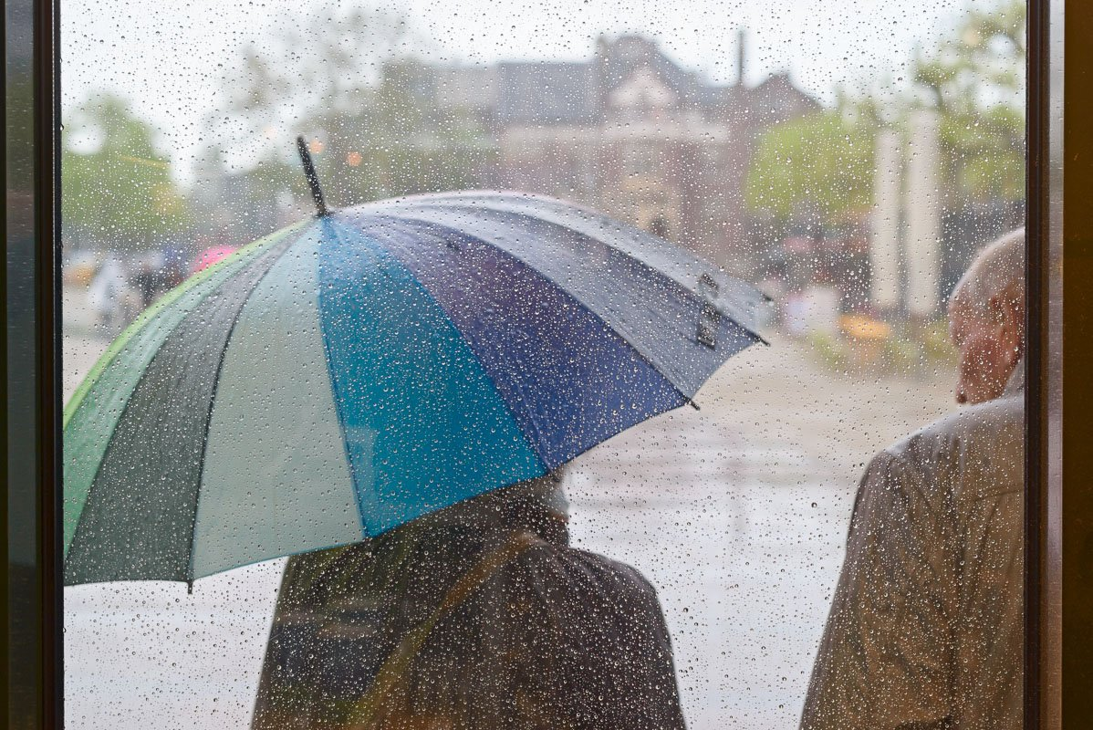 Regen in Amsterdam: schuilen onder een paraplu