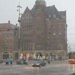 Een oranje tram in de stromende regen op de Dam in Amsterdam