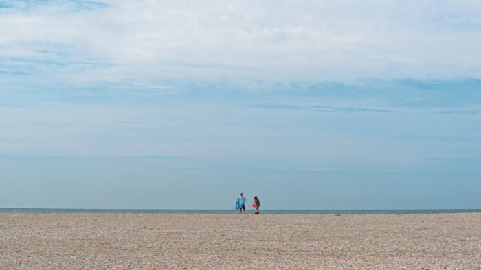Eenzame strandgangers op het strand van de Maasvlakte