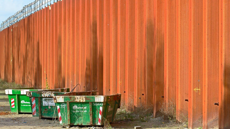 Vuilcontainers voor een roestige damwand langs het metrostation Isolatorweg