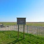 Een leeg mededelingenbord op de kade van de haven van Noordpolderzijl