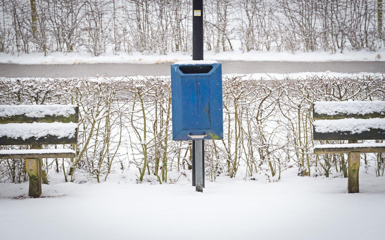 Symmetrie van bankjes met prullenbak in de winter sneeuw